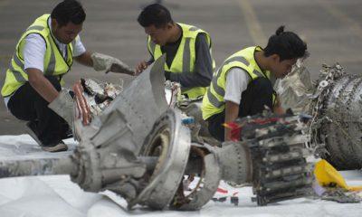 Các nhà điều tra xem xét mảnh vỡ của máy bay JT610. Ảnh: Getty.