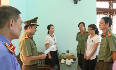 Bà Nguyễn Thị Hồng Nga, chuyên viên Phòng khảo thí và quản lý chất lượng Sở GD-ĐT Sơn La (mặc áo trắng bên phải), nghe tống đạt quyết định khởi tố bị can hôm 31-7-2018 - Ảnh: Công an cung cấp