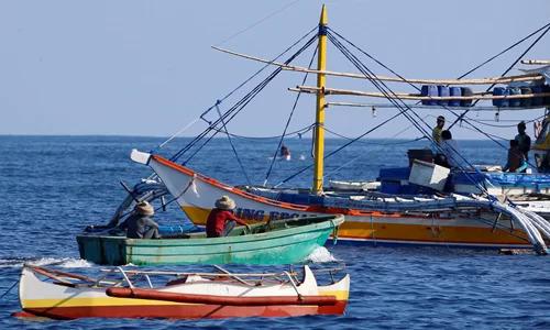 Thuyền của ngư dân Trung Quốc tiếp cận tàu cá Philippines trên Biển Đông. Ảnh: Reuters.