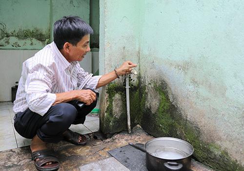 Ông Đặng Em chờ cả buổi sáng vẫn không hứng được nước. Ảnh: Nguyễn Đông.