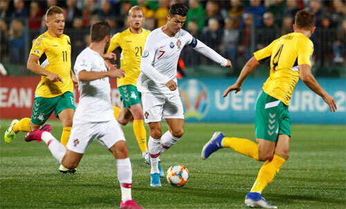 Ronaldo đi bóng trong vòng vây của các cầu thủ Lithuania.