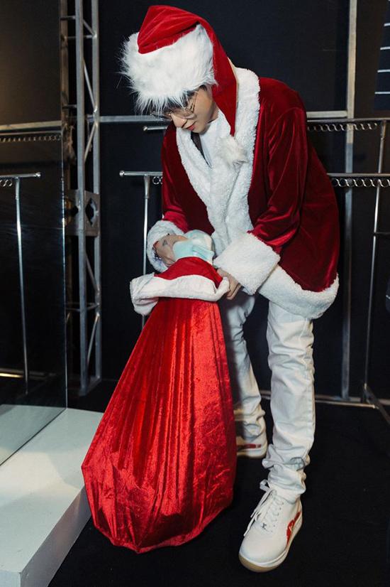 Anh diện trang phục của ông già Noel và mang theo một túi quà to.