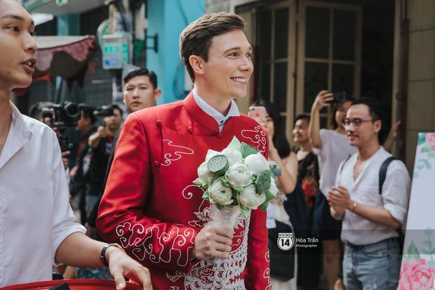 Chú rể Jack diện áo dài đỏ, cầm hoa sen, cùng gia đình tới nhà MC Hoàng Oanh làm lễ rước dâu theo đúng nghi thức truyền thống.