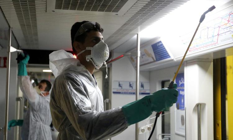 Một công nhân dọn dẹp toa tàu để phòng chống dịch Covid-19 ở Tehran, Iran hôm 26/2. Ảnh: AFP.