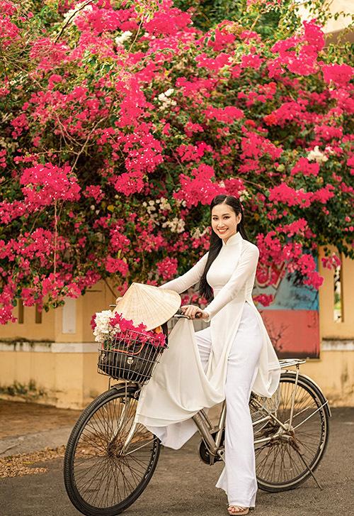 Đoàn Hồng Trang duyên dáng trong tà áo dài trắng đạp xe dạo phố khi về thăm quê. Mùa này những giàn hoa giấy đang nở rộ rực rỡ ở nhiều góc đường.