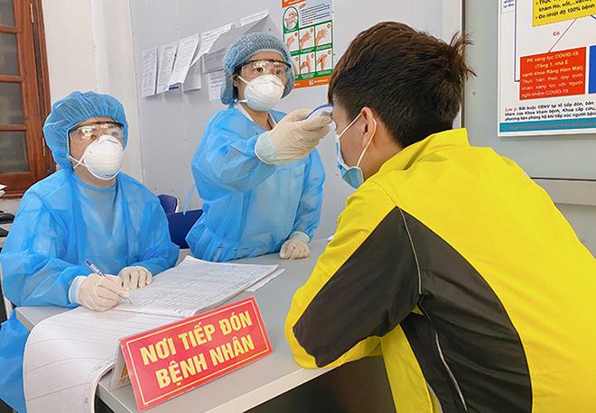 Bác sĩ Trọng đang điều tra dịch tễ kết hợp với điều dưỡng đang đo nhiệt độ cho người bệnh. Ảnh: Thùy An