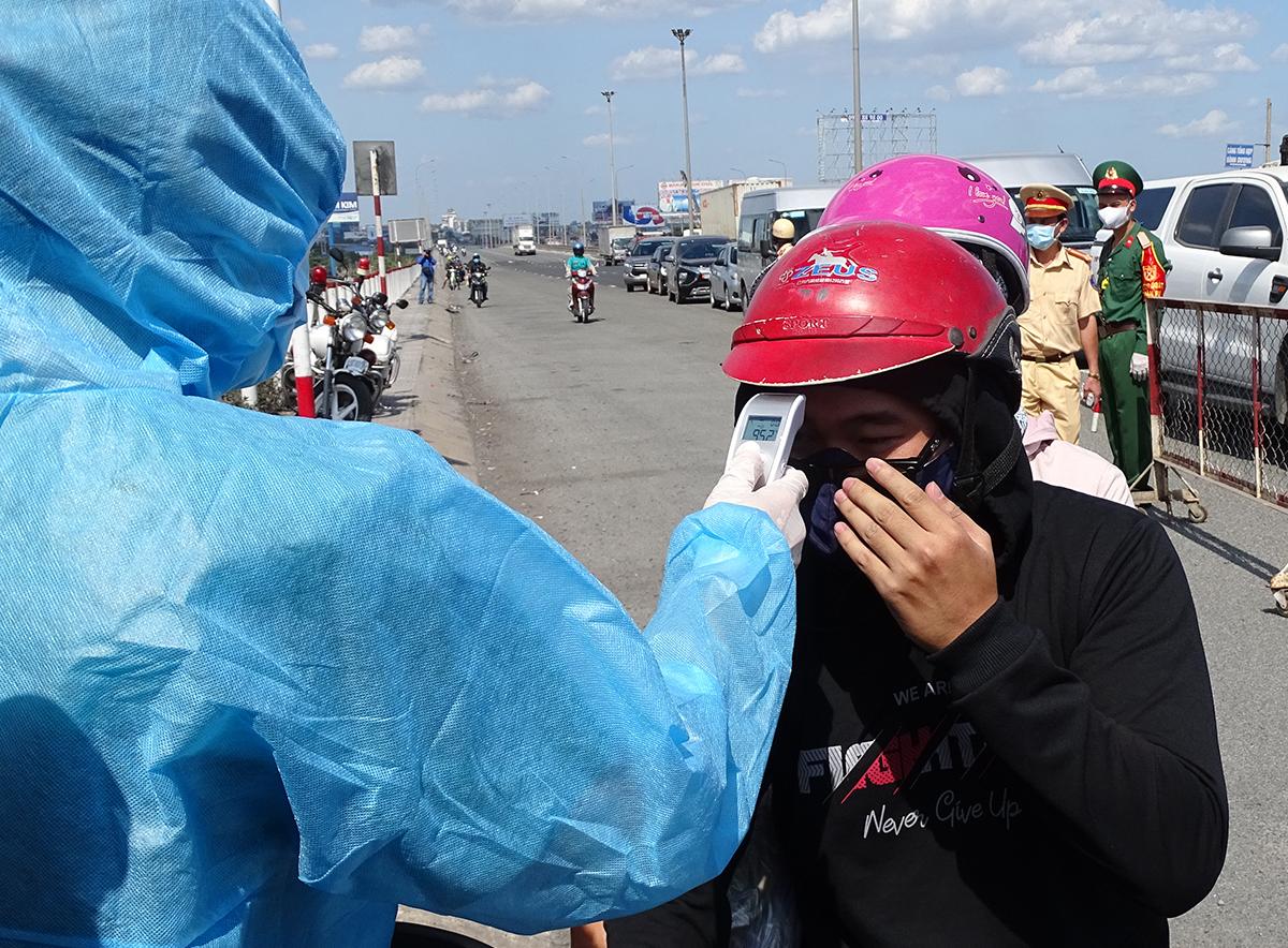 Người đi từ Đồng Nai vào TP HCM phải đo thân nhiệt, nếu không có dấu hiệu bất thường sẽ được đi. Ảnh: Hà An.