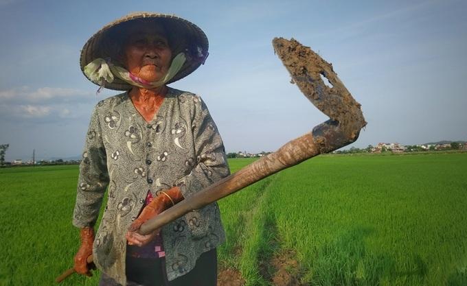 Bà Nguyễn Thị Điểu, 84 tuổi, và chiếc cuốc dùng để tháo nước tưới đồng. Ảnh: Phạm Linh.