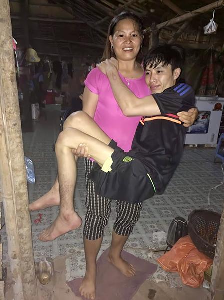 Chồng bị liệt hai chân, năm đầu tiên, chị Bùi Thị Hoa thường phải bế chồng phục vụ sinh hoạt cá nhân. Ảnh: Nhân vật cung cấp.