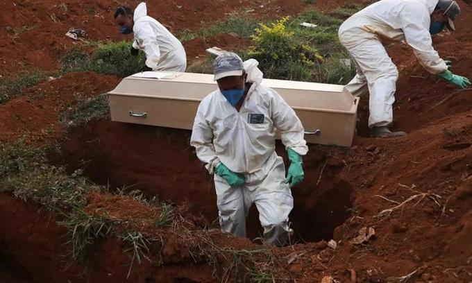 Những người đào mộ mặc đồ bảo hộ chuẩn bị chôn cất quan tài một nạn nhân Covid-19 trong tang lễ không có người thân ở Sao Paolo, Brazil hom 22/5. Ảnh: AFP.