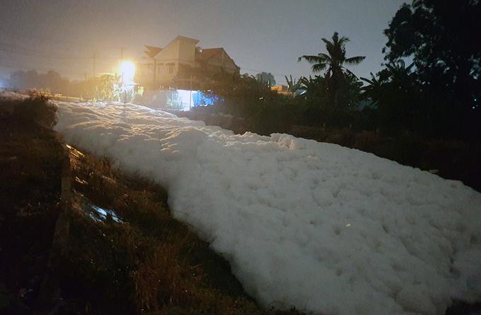 Kênh Suối Gạo nổi bọt trắng xoá kéo dài hàng trăm mét tối 8/4. Ảnh: Thái Hà