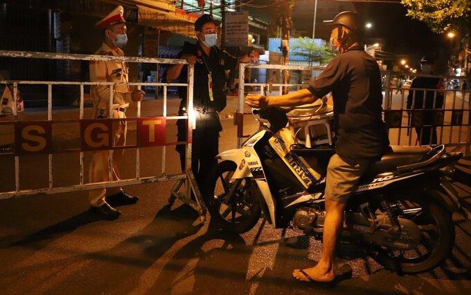 Lực lượng công an kéo rào chắn thực hiện cách ly y tế trên đường Hải Phòng, cách Bệnh viện Đà Nẵng khoảng 100 m, lúc 0h ngày 28/7. Ảnh: Nguyễn Đông.