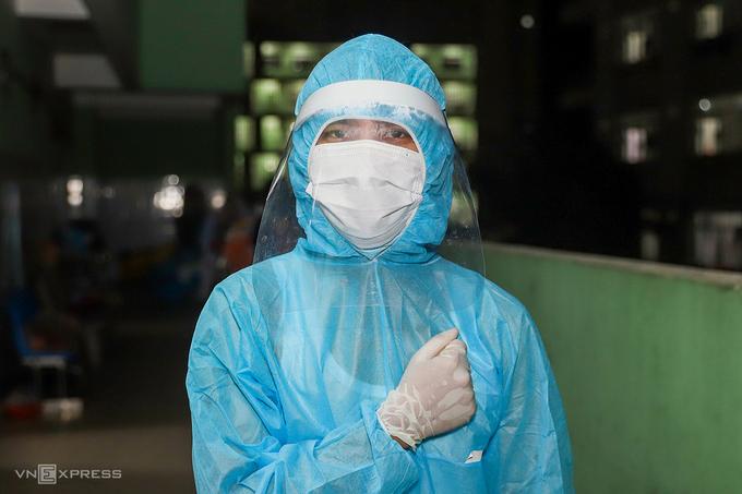 Một chiến sĩ phòng hóa học nhận nhiệm vụ phun hóa chất khử khuẩn trong Bệnh viện Đà Nẵng, đặt tay lên ngực thể hiện quyết tâm, ngày 26/7. Ảnh: Nguyễn Đông.