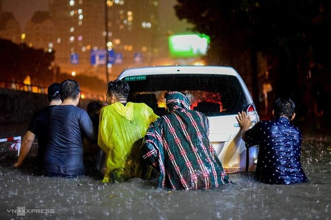 Người đi đường và dân trong khu vực dầm mưa, hợp sức giúp tài xế đẩy ôtô qua đoạn ngập sâu.