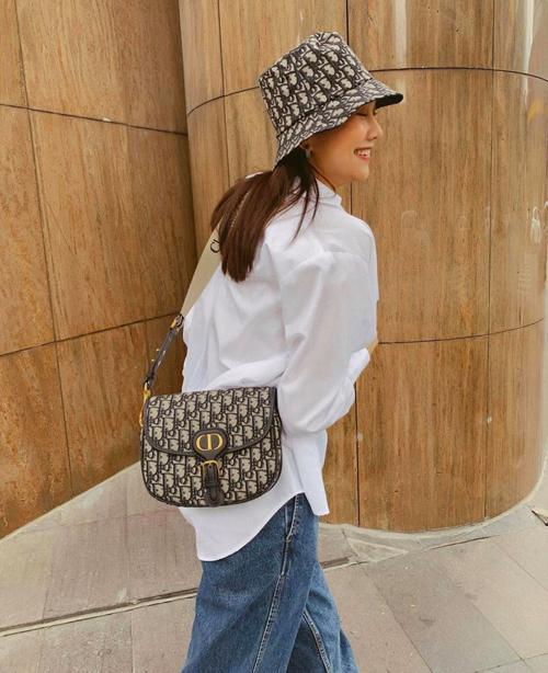 Diện trang phục đơn giản với sơ mi trắng, quần jeans nhưng Thanh Hằng giúp set đồ bắt mắt hơn với nguyên bộ phụ kiện gồm mũ rộng vành, túi đeo chéo của Dior.