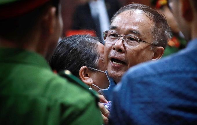 Người thân khóc, ôm ông Nguyễn Thành Tài trước khi các bị cáo được đưa về trại giam, trưa 19/9. Ảnh: Hữu Khoa.