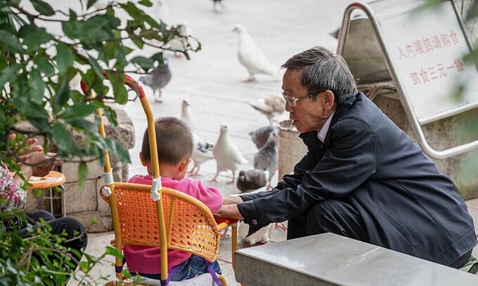 Một người ông đang chăm cháu ở tỉnh Vân Nam. Ảnh: Wan Huizhou/People Visual.