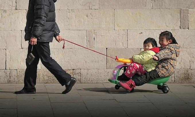 Một người ông dẫn hai cháu đi chơi trên xe đẩy đồ chơi ở Nam Kinh, tỉnh Giang Tô. Ảnh: People Visual.