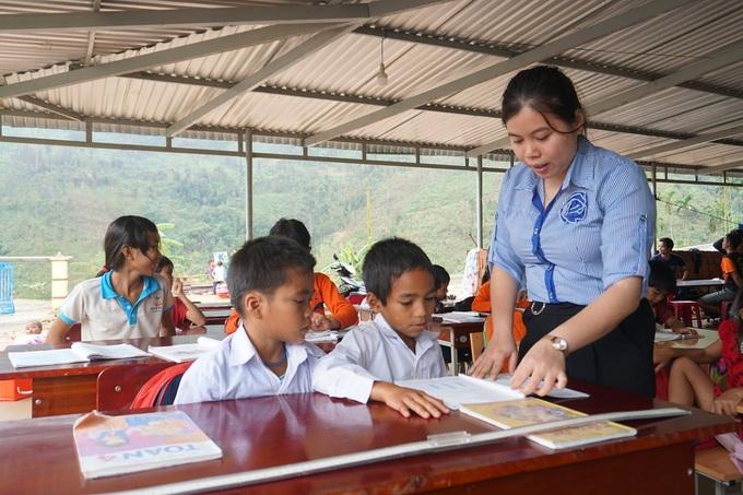 Cô giáo Hà My dạy học dưới hiên nhà dân gần điểm trường bị sạt lở. Ảnh: Phạm Linh.