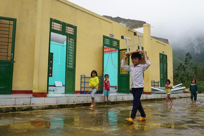 Sau giờ học, em Hồ Văn Sơn mang ghế từ nhà dân về cất ở phòng còn lại của trường. Ảnh: Phạm Linh.