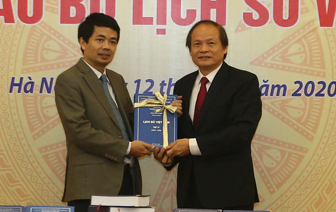 GS Nguyễn Văn Khánh (bìa phải) bàn giao bản thảo cho ông Đỗ Tiến Dũng, Giám đốc Quỹ Nafosted. Ảnh: Đình Nam.