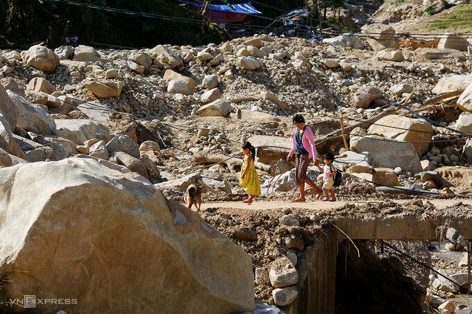 Người dân đi qua ngôi làng ở thôn 2 xã Phước Thành, giờ chỉ còn là đống đất, đá. Ảnh: Nguyễn Đông.