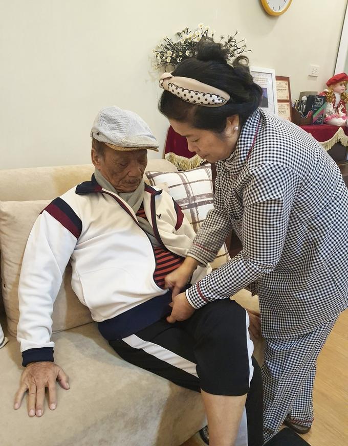 Bà Minh Ngà cẩn thận đeo khăn, cài áo cho chồng. Ảnh: Hoàng Huế.