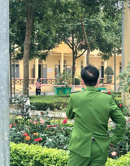 Thượng tá Hải đi tuần tra điểm cách ly trên địa bàn, tranh thủ nhìn vợ đang cách ly tại tiểu đoàn 3, trung đoàn 2, Chí Linh. Giây phút cặp vợ chồng gửi lời của gió cho nhau được một người quen chụp lại. Ảnh: Nhân vật cung cấp.