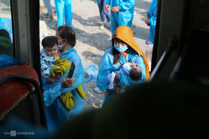 Lao động hồi hương về các tỉnh phía Bắc, miền Trung được hội nhóm tình nguyện Đà Nẵng chở bằng xe khách tại điểm tập kết nam hầm Hải Vân, hôm 9/10. Ảnh: Nguyễn Đông