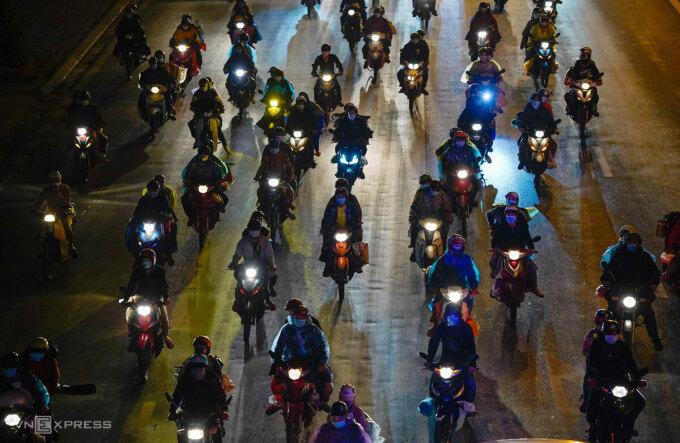 Người lao động chạy sau xe cảnh sát giao thông Hà Nội dẫn đường để về các tỉnh phía Bắc, đêm 5/10. Ảnh: Phạm Chiểu